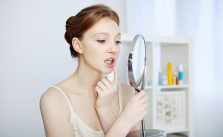 Woman checking bleeding gums in the mirror